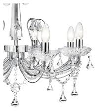 attached to curved arms finished in chrome with delicate chain links and elaborate crystal ons and detailing around a decorative crystal column