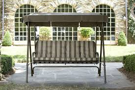 exterior black metal patio swing with grey fabric canopy and grey striped seat in the