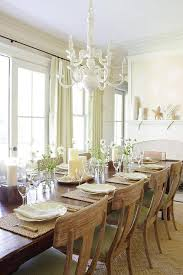beige and green dining room features a glossy white chandelier illuminating a long rustic dining table lined with distressed klismos dining chairs accented