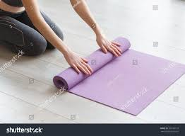 young yoga woman rolling her lilac mat after a yoga class on wooden floor near a