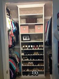 interior white wooden closet shelves with shoes rack plus white clothes hook with rod on