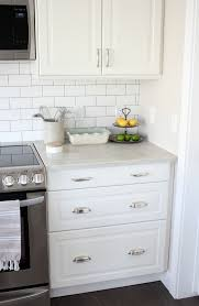kitchen makeover with white ikea kitchen cabinets subway tile backsplash and marble quartz countertop
