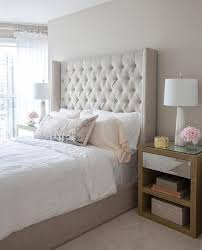 Beige tufted wingback bed dressed in white linen bedding flanked