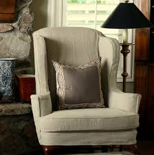 how to custom reupholstery wingback chair covers with tan fabric and floor lamp also window treatment