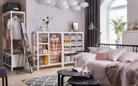 White and pink open plan living room with white open storage across the  back wall.