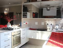 a white high gloss kitchen design with a large mirror