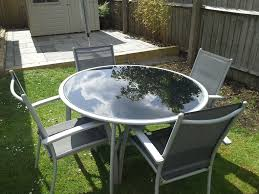 round black glass top garden table and 4 chairs