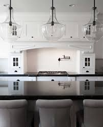 teriffic pot filler faucet with clear glass pendant lighting and white kitchen cabinet also kitchen island