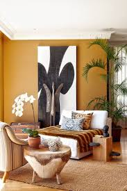 Shades of ocher, carvings of wood and the artworks make this living room  terrific