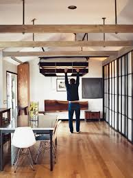 a man is pulling down a bed from the ceiling in a small apartment