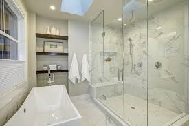 white marble dominates this master bath giving it a bright widening look while the solid glass