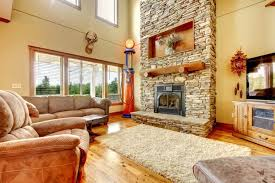 An eclectic living room with a plush white rug and an enormous stone  fireplace that extends
