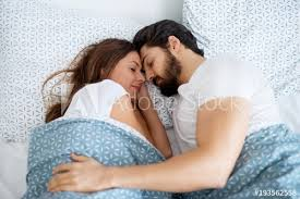 beautiful romantic couple in love sleeping together hugged on the bed at home or hotel