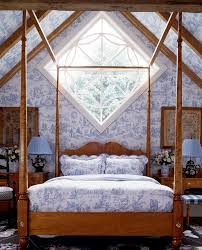 bright toile bedding in bedroom farmhouse with blue and white bedding next to wooden beams alongside high vaulted ceilings and blue and white wallpaper