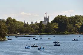 people relax on boats on the serpentine lake in london england