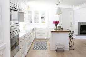 beautiful kitchen features a pair of white and gold pendants oversized cone shade pendants illuminating a wood top island lined with crate and barrel tig