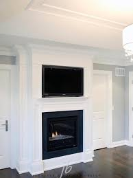 sallyl bedroom with flatscreen tv over gas fireplace elegant white wood paneled fireplace with
