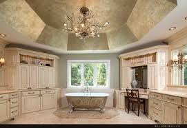 this classy bathroom features intricate designs on the bathtub and a large textured ceiling chandelier over