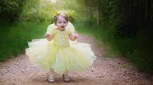cute baby girl is wearing yellow dress ...