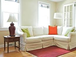 apartment sized furniture living room l shaped sectional with white slipcover and fun colored accent pillows red rug vintage styled side pretty blue