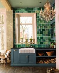 a grey kitchen with a large scale green tile backsplash extended on the whole wall