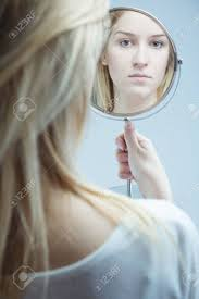 woman holding hand mirror. Close-up Of A Young, Upset Woman Looking In The Mirror She Is Holding Hand