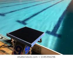 a starting block number 9 of outdoor swimming pool with empty racing lane in