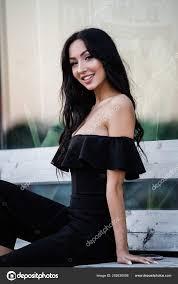 portrait beautiful young brunette woman black dress stylish makeup sitting stock photo