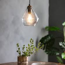 a prism shaped glass pendant light with a brass bulb fitting and black cord