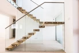 Floating staircase with thick treads and a glass balustrade modern-staircase