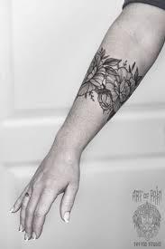 татуировка женская графика на предплечье браслет из цветов пиона