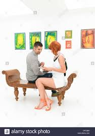 people sitting at table white background. stock photo - people sitting on a wooden bench, indoors, with colorful artworks displayed white wall in background at table p
