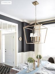 a lantern style chandelier gets an elegant update with the addition of white chandelier shades