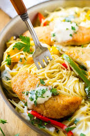a fork serving up a portion of en scampi pasta with peppers and creamy sauce