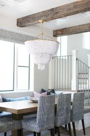 lovely dining nook boasts rustic wood ceiling beams and a white beaded chandelier hanging over a built in banquette window seat facing a chunky wood dining