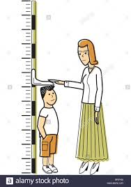 A Woman Measuring A Boy Against A Growth Chart Stock Photo