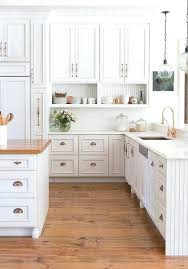 amazing kitchen features white raised panel cabinets adorned with copper hardware paired marble antique cabinet