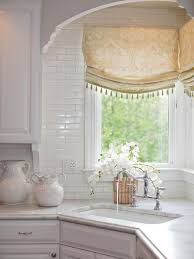 sink windows window love: a corner sink takes center stage in this white traditional kitchen beaded roman shades add