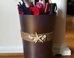 diy umbrella holder or trashcan-black cans spray paint(blue, brown,  gold)/twine/shells = no more umbrellas stuck on the front porch! and since  it's a solid ...