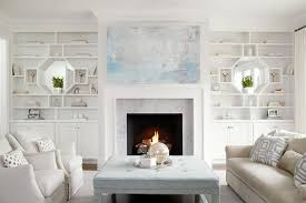 elegant and sophisticated living room boasts a blue abstract canvas art piece placed over a white fireplace mantel accented with a carrera marble surround
