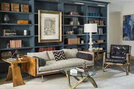 living room lamp tables. a bold and masculine living room with large built-in blue bookcases behind the wood lamp tables