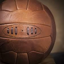 vintage sports genuine leather football on oak plinth