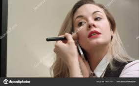 young beautiful woman applying makeup on face with brush having phone call being late