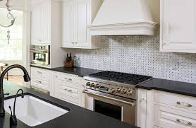 kitchen with black granite counter and white basketweave backsplash tile and white cabinetry