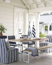 we love this coastal patio with striped slipcovered chairs a picnic table and