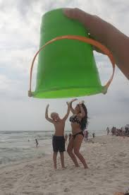 interior funny beach photography ideas with two people under big green pail on hand people
