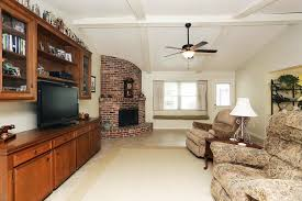 exposed brick corner fireplace design with white vaulted ceiling for traditional living room ideas