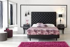 floral patterned bedding idea beneath tall decorative black tufted  headboars above white pillows between black nighstand
