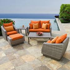 image modern wicker patio furniture. pretty orange cushions on modern wicker outdoor furniture in poolside patio with stone flooring image a