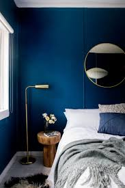 Gorgeous dark blue walls and blush accents for a dramatic bedroom. If you're